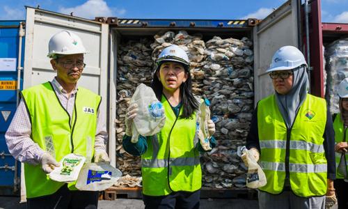 Bộ trưởng Năng lượng, Công nghệ, Khoa học, Biến đổi khí hậu và Môi trường Malaysia Yeo Bee Yin (giữa) đứng trước các container chứa rác thải nhựa tại cảng Klang hôm nay. Ảnh: AFP.